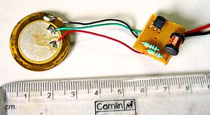 Buzzer - Interior of a readymade buzzer,  showing a piezoelectric-disk-beeper (With 3 electrodes ... including 1 feedback-electrode ( the central, small electrode joined with red wire in this photo), and an oscillator to self-drive the buzzer.
