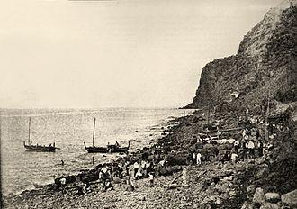 Calheta, Madeira - A historical image of the rocky beach of Calhau da Calheta, as workers transport barrels of Madeira wine for shipment