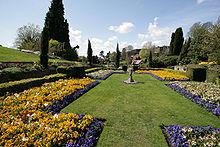Jardín formal con césped recortado, parterres y zócalo de piedra bajo un cielo despejado