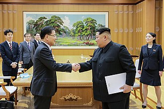 2018 North Korea–United States Singapore Summit - Chung Eui-yong (left), the South Korean national security chief, and Kim Jong-un meeting in Pyongyang on March 5, 2018. Kim is holding a letter from President Moon Jae-in arranging for direct peace talks.