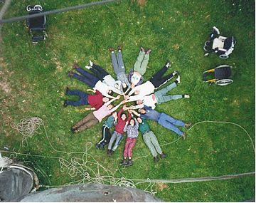 Circle of friends: seen from above, participants lie in a circle on the grass at the foot of a cliff, with their hands stretched out to meet in the middle