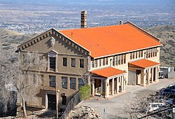 A large three-story building with many windows and an orange tile roof is perched on a hillside overlooking a wide valley far below.