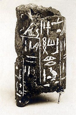 Broken cylinder of dark grey stone with white hieroglyphs inscribed on it