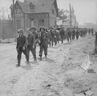 185th Infantry Brigade (United Kingdom) - German prisoners being escorted back through La Brèche d'Hermanville, France, by men of the 2nd Battalion, King's Shropshire Light Infantry, 6 June 1944.