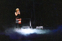 Faraway image of a woman in a short red skilt and black top standing on a stage. Smokes billow around her feet.