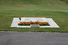 Ein Grab, das von einer abgewinkelten Marmorplatte mit den Namen Diefenbakers und seiner Frau markiert ist und von Pflanzungen kleiner Ringelblumen und einer zusätzlichen Bronzetafel umgeben ist.  Dahinter erstreckt sich ein Rasen.