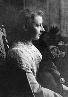 Monochrome photograph of a young woman, wearing a lace trimmed top, and seated, facing right. She has a small dog on her lap, which is facing in the same direction.