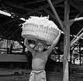 Een boslandcreooljongen in de houtzagerij met een mand met houtsnippers, Bestanddeelnr 252-4837.jpg