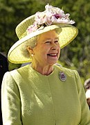 Photographie en plan taille de la Reine vêtue de jaune.