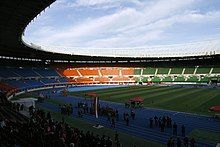 An oval shaped stadium with a blue athletics track and stands with red, blue, orange and green seating sections. One of the lateral stands is filled and more people are in the track. The sky is blue with clouds.