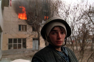 First Chechen War - A Chechen stands near a burning house in Grozny.