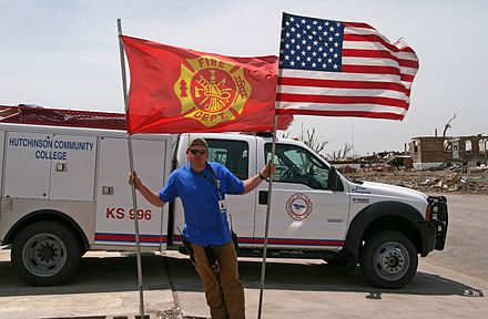 FEMA--33068--Greensburg fire chief holding up flags in rural Kansas after a tornado destroyed the town FEMA - 33068 - Greensburg fire chief holding up flags in Kansas.jpg