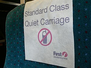 "Etiquette in technology - A headrest cover in the ""quiet carriage"" of a British intercity train, reminding passengers that mobile phones must not be used in this carriage"