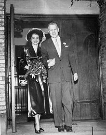 Um homem em um terno leva uma mulher de transporte de flor pela mão, caminhando para fora de uma capela.