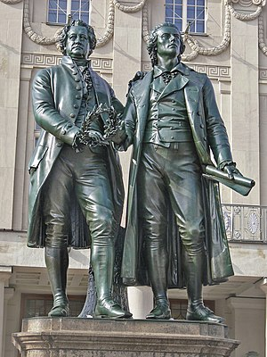 Photograph of a statue of Goethe and Schiller standing side by side, each looking forward. The statue is in front of the stone facade of an elaborate building. They are of nearly the same height. Goethe appears middle-aged; Schiller is noticeably younger. They are dressed in nineteenth century clothing. Goethe is wearing a knee-length formal coat, and Schiller is wearing a calf-length coat. Both men wear breeches. Goethe's left hand rests lightly on Schiller's shoulder; his right hand holds a laurel wreath near his waist. Schiller's right hand is nearly touching the wreath, which may suggest that Goethe is passing the wreath to Schiller. Schiller's left hand extends loosely below his waist, and grasps a rolled sheet of paper.