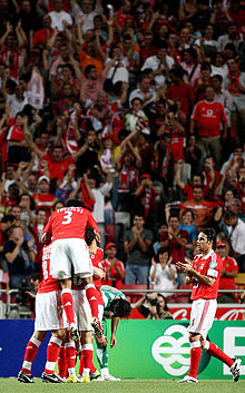 Players celebrating a goal in front of  fans wearing red, the team color