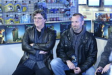 Two men wearing black leather jackets are sitting in chairs, surrounded by Halo-themed Xbox 360s and accessories. One person with the same attire is cutoff from the picture.