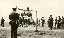High jumper watched by a crowd of people, most wearing dark military uniforms with peaked caps