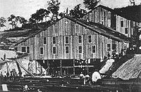 Two large wooden buildings, each about 60 to 80 feet across, are being constructed into a hillside. About five people stand on the roof of the nearest building while below, upwards of 15 people stand amidst piles of long timber. The exteriors of the buildings appear to be almost complete, with only the lower third of the nearest building still showing exposed framing.