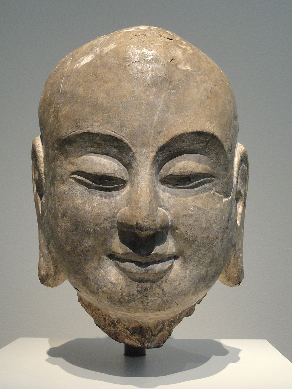Sculpture of head of smiling monk with East Asian traits, part of limestone sculpture