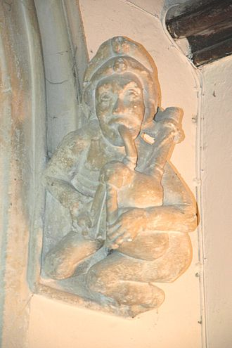 Horspath - St Giles' parish church: 15th century carved stone figure of a man playing bagpipes, forming the right label stop of the tower arch