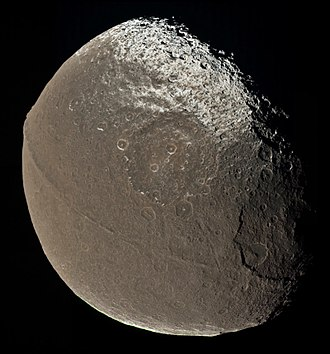 Iapetus (moon) - Natural color photomosaic combining Cassini images taken on 31 December 2004. It shows the dark Cassini Regio and its border with the bright Roncevaux Terra, several large craters (Falsaron above center, Turgis, the largest, at right), and the equatorial ridge (the Toledo and Tortelosa Montes).