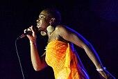 Eine Frau, die ein orangefarbenes Kleid trägt, während sie in ein Mikrofon singt.