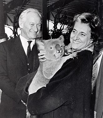 Arthur Tange - Indian Prime Minister Indira Gandhi holding a koala at Taronga Zoo in 1968, with Arthur Tange, Australian High Commissioner to India, in the background.