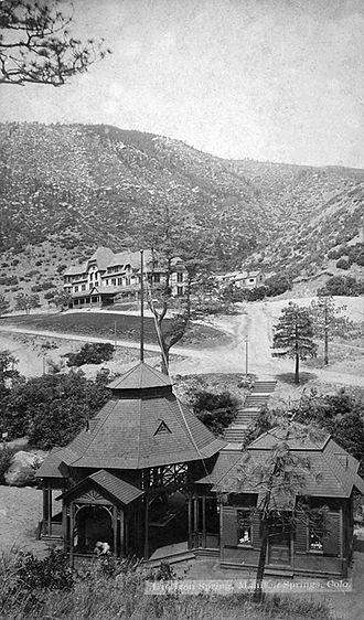 Iron Springs, Colorado - Ute Iron Spring, Gazebo and curio shoppe. Iron Springs Hotel in background. Photograph courtesy: Manitou Springs Heritage Center.