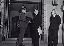Black and white photograph of a man wearing military uniform shaking the hand of a man in a formal suit. The two men are standing in front of a stone gateway, and another man wearing a formal suit is looking on from the right of the image.
