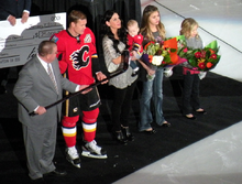 A man in a red hockey uniform accepts a silver stick from another man in a grey suit as his wife and three young daughters stand beside.