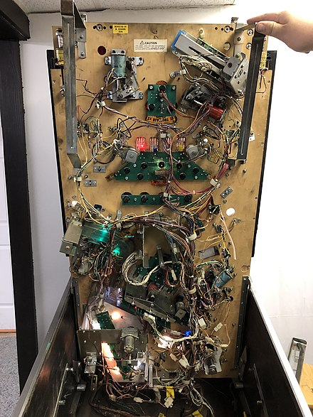 The underside of a 1990s pinball machine, showing a variety of mechanical and electrical components.