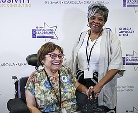 A photograph of Judy Heumann in her power chair next to Barbara Ransom. They are holding hands and smiling, standing in front of a sponsor banner.
