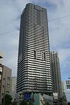 Ground-level view of a white, rectangular high-rise; the corners are cut and balconies form horizontal stripes up the height of the tower
