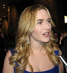 A young woman with shoulder-length, wavy, blonde hair and wearing a low-cut blue gown, is looking to the right with her mouth open as if speaking.