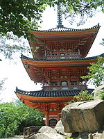 Three-storied pagoda with white walls and red beams. There are railed verandas on the two upper stories.