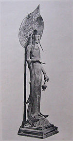 Three-quarter view of a very slim and tall statue carrying a vase in with two fingers of her left hand. Her right arm is bend with the palm of her right hand facing upward. A halo on a pole is seen behind the statue.