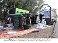 Laborers unload a truck that overurned on the multan Road early on Sunday due to fog DNA.jpg
