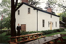 A white house in three-quarter perspective.  In the foreground are several picnic benches.  To the left is a tall tree with a man standing beside it.  To the right, partly obsured by the house, is an old well.
