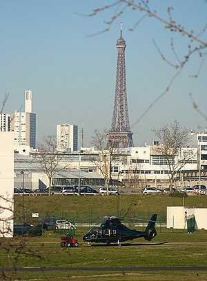 Issy-les-Moulineaux - An Eurocopter AS365 Dauphin taking off from the heliport, with the Eiffel tower behind.