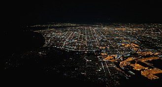 San Pedro, Los Angeles - In this night-time aerial photograph of Los Angeles, San Pedro is in the center and right foreground, including part of the brightly lit Terminal Island. The dark peninsula to the left of San Pedro is Palos Verdes.