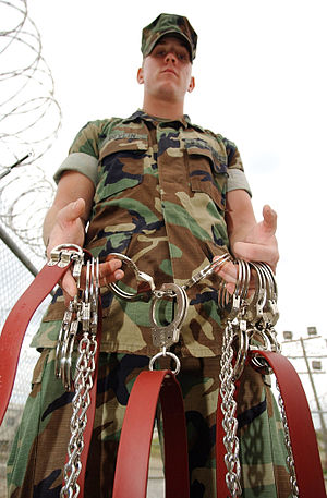 Prison officer - U.S. Marines military police officer shows restraints used for transporting detainees at Camp X-Ray, Guantanamo Bay, Cuba (January 10, 2002).