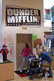 "Three adults and a child in a stroller in front of a set of closed elevator doors. Above them is a sign with ""Dunder Mifflin Paper Company"" on it in white letters on a black background"