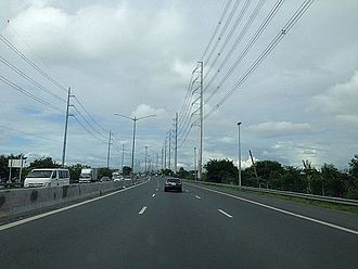 Manila–Cavite Expressway - Manila–Cavite Expressway looking northbound near Zapote in Las Piñas. The Dasmariñas-Las Piñas transmission line of National Grid Corporation of the Philippines and subtransmission lines by Meralco lie on both sides of the expressway at this segment.