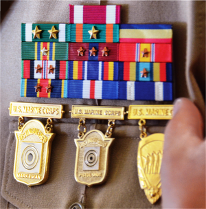 Marksmanship badges (United States) - Above are three marksmanship competition badges on a U.S. Marine Corps service uniform; from left to right: Distinguished Marksman Badge, Distinguished Pistol Shot Badge, and the Inter-Division Pistol Competition Badge.