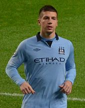 Short-haired young man on a field wearing a light-blue sports jersey.