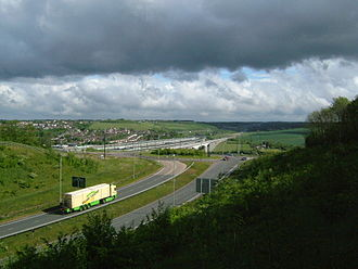 M2 motorway (Great Britain) - Junction 2 of the M2, the roundabout on the A228, showing the motorway crossing the Medway and climbing up the Nashenden Valley. Alongside is High Speed 1.