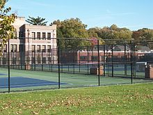 picture of a fence, with tennis courts behind them, with a three- story brick building in the background.