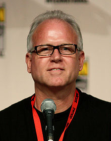 A man with grey hair and glasses sitting in front of a microphone.