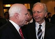 John McCain talking with Joe Lieberman in a narrow, busy hallway at a conference